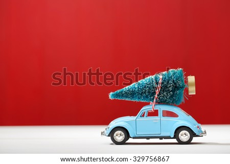 Miniature car carrying a Christmas tree on red colored wooden wall - stock photo