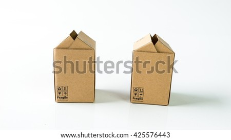 Miniature cardboard boxes with Fragile wording symbol. Concept of handle with care courier business. Isolated on white background. Slightly de-focused and close-up shot. Copy space. - stock photo