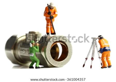 Miniature construction workers plumbing valve - stock photo