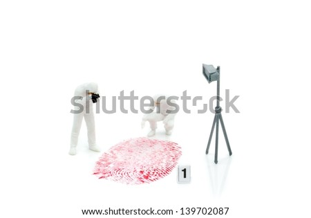 Miniature crime investigators photographing a finger print - stock photo