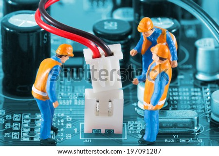 Miniature engineers fixing wire connector of circuit board. Computer repair concept. Close-up view. - stock photo
