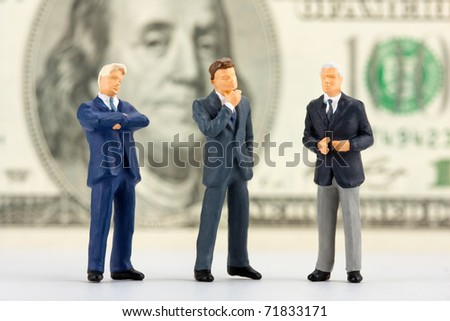 Miniature figurines of successful business team with $100 banknote on background - stock photo