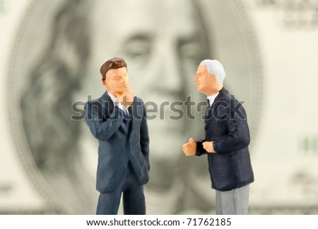Miniature figurines of two discussing businessmen. Close-up view - stock photo