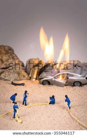 Miniature firemen at a car crash accident scene in flames - stock photo
