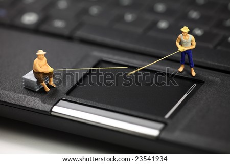 Miniature fisherman standing on a laptop computer representing online email phishing scams. Computer phishing and identity theft concept. - stock photo