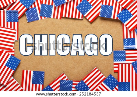 Miniature flags of the United States of America form a border on brown card around the name of the city of Chicago - stock photo