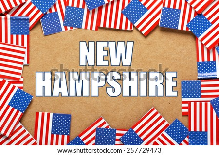 Miniature flags of the United States of America form a border on brown card around the name of the state of New Hampshire - stock photo