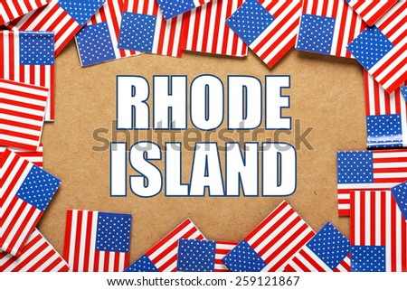 Miniature flags of the United States of America form a border on brown card around the name of the state of Rhode Island - stock photo