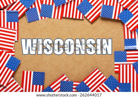 Miniature flags of the United States of America form a border on brown card around the name of the state of Wisconsin - stock photo