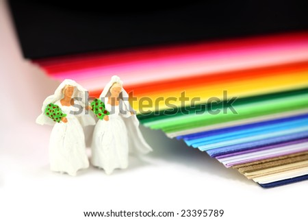 Miniature homosexual couple in wedding dresses standing next to rainbow colored paper. Gay/same sex marriage concept. - stock photo