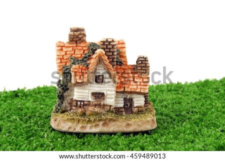 miniature house on green grass isolated on white - stock photo