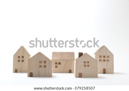 Miniature houses on white background. Building blocks arranged in row. - stock photo