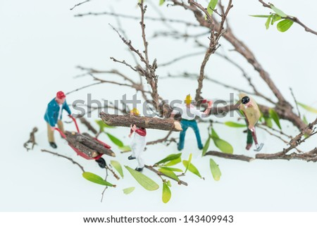 Miniature lumberjacks felling trees and carrying logs top view close up - stock photo