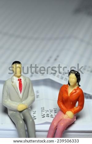 Miniature man and woman sitting on payroll - stock photo