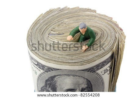 Miniature man drowning in a roll of American money. - stock photo