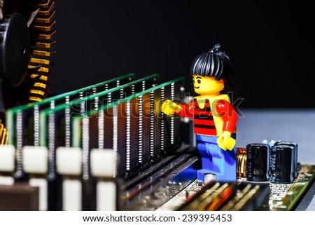 Miniature  man  figurine posing  on a computer motherboard - stock photo