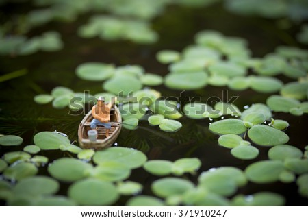 Miniature man fishing in a Fish pond - stock photo