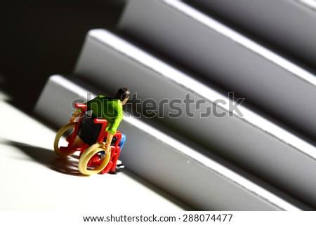Miniature man wheelchair access concept - stock photo