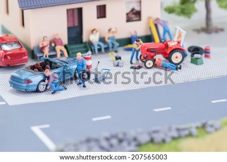 Miniature mechanics repairing a convertible car and a farm tractor close up  - stock photo