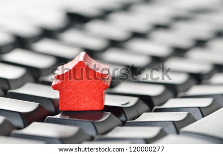 Miniature model home sitting on a computer keyboard. Web hosting or real estate on the internet concept. - stock photo