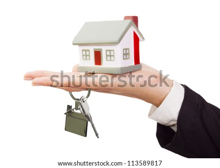 Miniature model house and keys resting on a female hand - stock photo