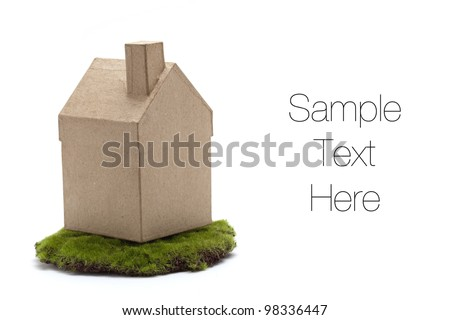Miniature model house resting on a green piece of land symbolize ecology concept, isolated on white - stock photo