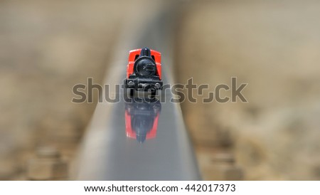 Miniature model of steam locomotive on real railway track - stock photo