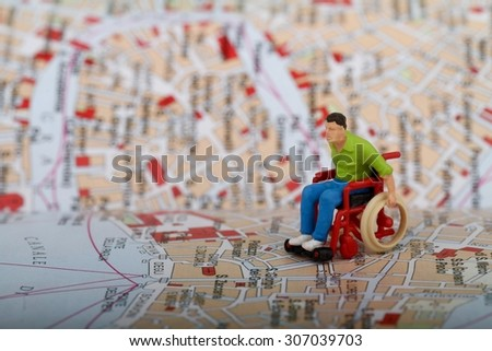Miniature of a disabled man on a wheelchair across a city map - stock photo