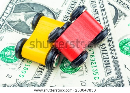 miniature of cars laying on dollar banknotes - stock photo