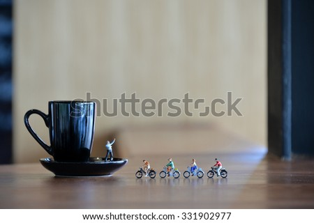 Miniature people cycling to a cup of coffee  - stock photo