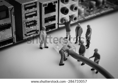 Miniature people  Network Engineers At Work - stock photo