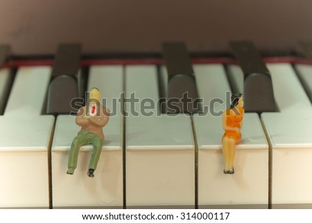 Miniature people of unhappy couple with piano background - stock photo