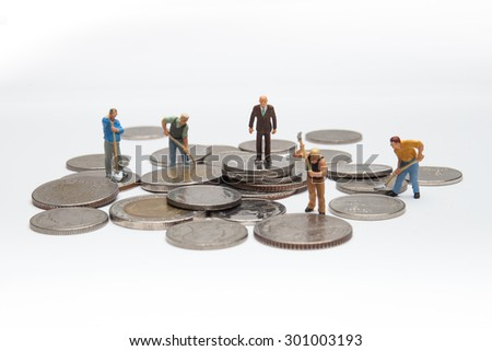 Miniature people on coins finance concept - stock photo