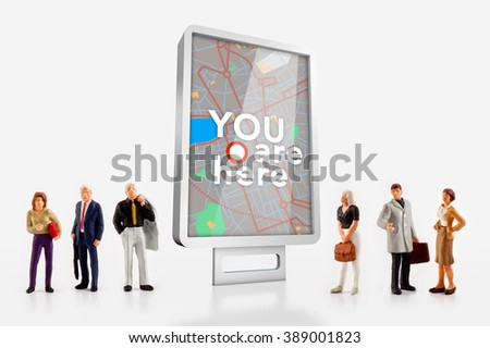 miniature people  - people standing in front of a billboard with a city map - stock photo