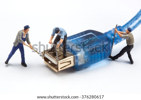 miniature people  - workers fixing a USB plug - stock photo