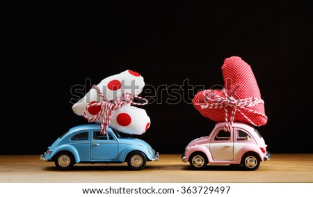 Miniature pink and blue cars carrying heart cushions - stock photo