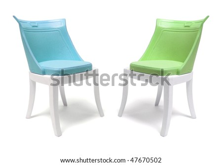 Miniature Plastic Chairs on White Background - stock photo