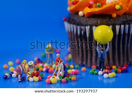 Miniature Plastic People Cleaning Up a Messy Cupcake - stock photo