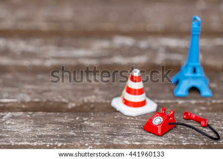 miniature red vintage telephone and stop sign with traffic cone on grunge wooden floor. - stock photo