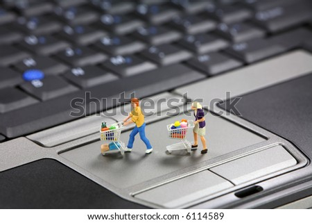 Miniature shoppers with shopping carts on a laptop touch pad mouse. Online shopping concept. - stock photo