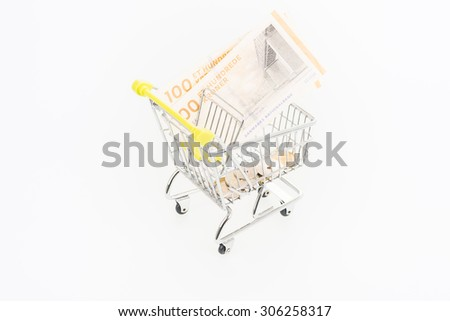 Miniature shopping cart with Danish Krone banknotes and coins over white background  - stock photo