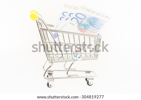 Miniature shopping cart with Euro banknotes close up - stock photo
