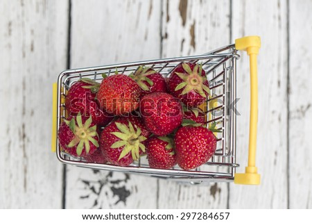 Miniature shopping cart with strawberries - stock photo