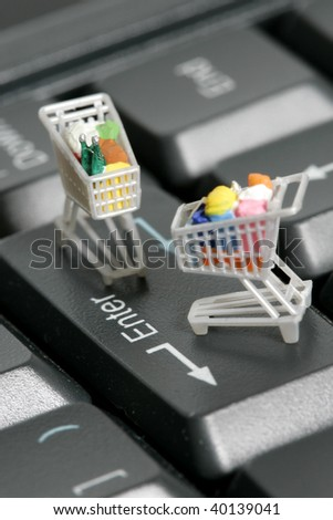 Miniature shopping carts on a computer keyboard - stock photo
