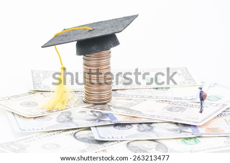 Miniature student with the mortarboard on top of a stacked of coins close up - stock photo