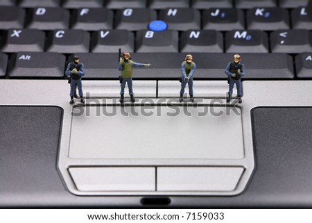 Miniature swat team is guarding a laptop from viruses, spyware and identity thieves. Computer security concept. - stock photo