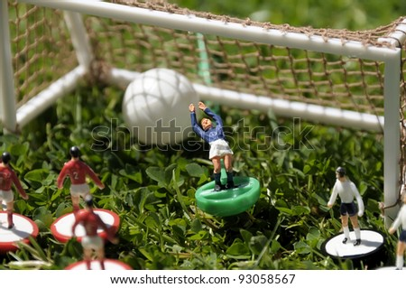 Miniature/table soccer game played on real grass to add more atmosphere. Short depth of field. - stock photo