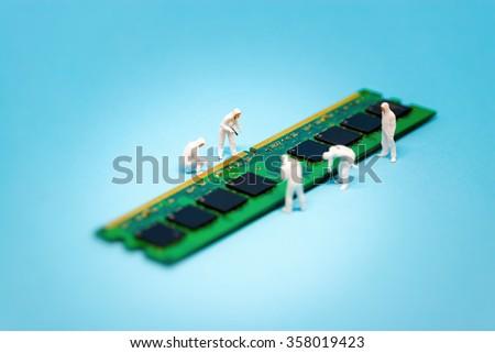 Miniature technicians repairing computer RAM module. Macro photo - stock photo