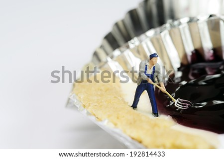 Miniature toy worker work with blueberry cheese pie - stock photo