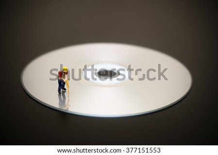 Miniature Worker On Top Of Compact Disc - stock photo